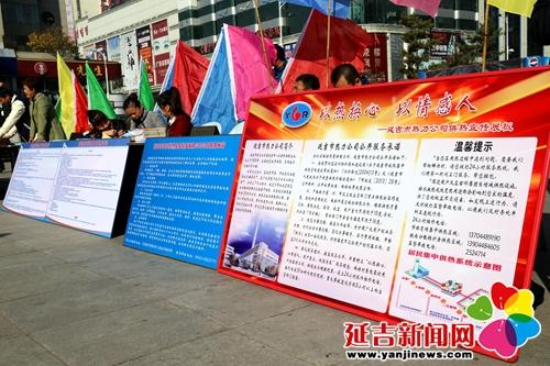 活动现场设立宣传展板,市住建局工作人员为过往市民发放供热宣传