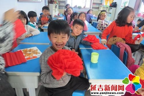 孩子展示折叠的大红花