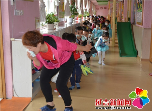 火险警报拉响后,幼儿园小朋友在老师的指引下,用毛巾捂住口鼻,弯腰